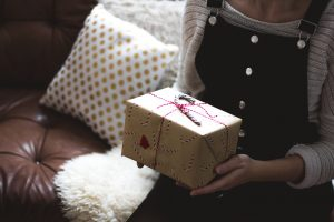 selective focus photography of woman holding gift box